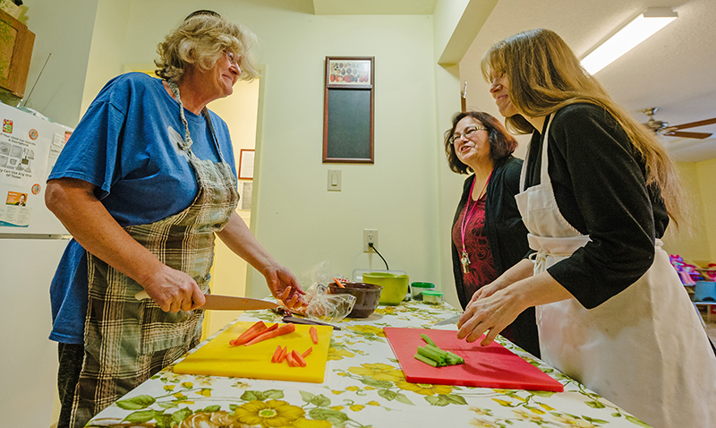 Two woman standing across a table from each other cutting vegetable