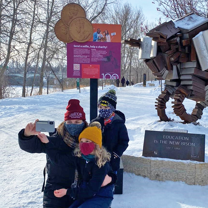 Woman and two young children posing for a selfie in front of sign and a sculpture